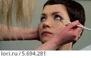Купить «Стилист делает макияж глаз молодой женщине», видеоролик № 5694281, снято 10 февраля 2014 г. (c) Иван Артемов / Фотобанк Лори