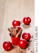 Купить «Свежие красные яблоки и корица в чашке на деревянном столе», фото № 5696001, снято 21 октября 2018 г. (c) BE&W Photo / Фотобанк Лори