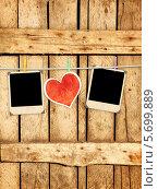 Купить «Два фотокарточки с красным сердцем на веревке на деревянном фоне», иллюстрация № 5699889 (c) Лукиянова Наталья / Фотобанк Лори