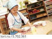 Купить «Девочка в детском саду. Дежурная по кухне. Помогает накрывать на стол», фото № 5702361, снято 7 апреля 2010 г. (c) Дмитрий Калиновский / Фотобанк Лори