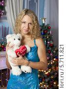 Купить «Девушка в синем платье с плюшевым медведем в руках на фоне новогодней ёлки», фото № 5711821, снято 12 июня 2013 г. (c) Литвяк Игорь / Фотобанк Лори