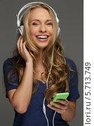 Позитивная девушка с длинными светлыми волосами слушает музыку в наушниках. Стоковое фото, фотограф Andrejs Pidjass / Фотобанк Лори