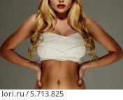 Купить «Блондинка с перебинтованной грудью стоит на сером фоне», фото № 5713825, снято 9 марта 2014 г. (c) Andrejs Pidjass / Фотобанк Лори