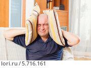 Купить «Злой мужчина закрыл уши подушками», фото № 5716161, снято 18 октября 2013 г. (c) Дарья Филимонова / Фотобанк Лори