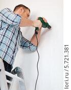 Купить «Рабочий сверлит стену при помощи электрической дрели», фото № 5721381, снято 28 января 2014 г. (c) Syda Productions / Фотобанк Лори