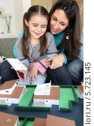 Купить «мама с дочкой смотрит макет дома», фото № 5723145, снято 21 января 2010 г. (c) Phovoir Images / Фотобанк Лори