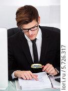 Купить «Бизнесмен анализирует документ с помощью увеличительной лупы», фото № 5726317, снято 19 октября 2013 г. (c) Андрей Попов / Фотобанк Лори