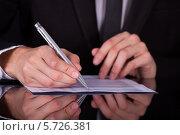 Купить «Бизнесмен делает пометки в документе», фото № 5726381, снято 19 октября 2013 г. (c) Андрей Попов / Фотобанк Лори