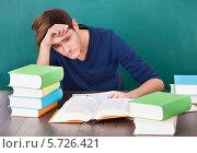 Купить «Уставший студент пытается заниматься», фото № 5726421, снято 19 октября 2013 г. (c) Андрей Попов / Фотобанк Лори
