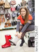 Купить «Счастливая женщина примеряет стильные резиновые сапоги», фото № 5726637, снято 14 февраля 2014 г. (c) Кекяляйнен Андрей / Фотобанк Лори