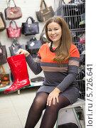 Купить «Женщина покупает красные резиновые сапоги», фото № 5726641, снято 14 февраля 2014 г. (c) Кекяляйнен Андрей / Фотобанк Лори