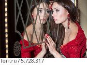 Купить «Девушка в красном платье смотрит в зеркало», фото № 5728317, снято 16 декабря 2012 г. (c) Losevsky Pavel / Фотобанк Лори