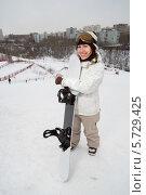 Купить «Девушка с доской для сноуборда стоит на снежном склоне на фоне города», фото № 5729425, снято 23 марта 2013 г. (c) Losevsky Pavel / Фотобанк Лори