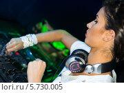 Купить «Девушка-DJ с наушниками на шее стоит за микшерным пультом в ночном клубе», фото № 5730005, снято 30 марта 2013 г. (c) Losevsky Pavel / Фотобанк Лори