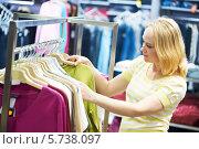 Купить «Девушка выбирает одежду в магазине», фото № 5738097, снято 1 марта 2012 г. (c) Дмитрий Калиновский / Фотобанк Лори