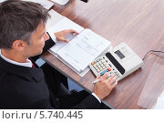Купить «Бизнесмен делает расчеты на калькуляторе», фото № 5740445, снято 10 ноября 2013 г. (c) Андрей Попов / Фотобанк Лори