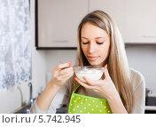 Купить «Счастливая женщина ест творог, стоя на кухне», фото № 5742945, снято 28 февраля 2014 г. (c) Яков Филимонов / Фотобанк Лори