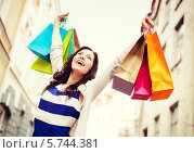Купить «Счастливая девушка подняла руки с разноцветными пакетами вверх, радуясь удачному шопингу», фото № 5744381, снято 29 июня 2013 г. (c) Syda Productions / Фотобанк Лори