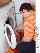 Купить «Женщина укладывает бельё в стиральную машину», фото № 5747097, снято 27 марта 2014 г. (c) Ольга Марк / Фотобанк Лори