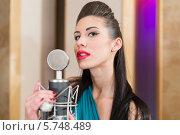 Купить «Красивая женщина поет в микрофон в студии», фото № 5748489, снято 25 декабря 2012 г. (c) Losevsky Pavel / Фотобанк Лори