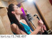 Купить «Красивая брюнетка поет с микрофоном в студии звукозаписи», фото № 5748497, снято 25 декабря 2012 г. (c) Losevsky Pavel / Фотобанк Лори