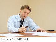 Купить «Бизнесмен сидит за столом в офисе и подписывает документы», фото № 5748581, снято 2 декабря 2012 г. (c) Losevsky Pavel / Фотобанк Лори