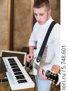 Купить «Счастливый мужчина играет на гитаре возле синтезатора», фото № 5748601, снято 25 декабря 2012 г. (c) Losevsky Pavel / Фотобанк Лори