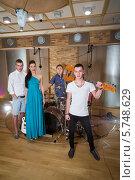 Купить «Музыкальная группа из трех парней и девушки в студии звукозаписи с музыкальными инструментами», фото № 5748629, снято 25 декабря 2012 г. (c) Losevsky Pavel / Фотобанк Лори