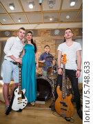 Купить «Портрет музыкальной группы из трех парней и девушки в студии звукозаписи с музыкальными инструментами», фото № 5748633, снято 25 декабря 2012 г. (c) Losevsky Pavel / Фотобанк Лори