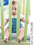 Купить «Малыш смотрит сквозь оградительную стенку кроватки», фото № 5749345, снято 27 марта 2013 г. (c) Losevsky Pavel / Фотобанк Лори