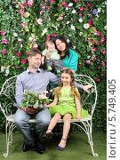 Купить «Счастливая молодая семья с двумя детьми сидит на плетеной скамейке в цветущем саду», фото № 5749405, снято 13 января 2013 г. (c) Losevsky Pavel / Фотобанк Лори