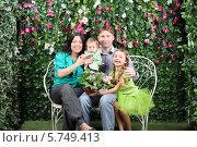 Купить «Счастливая молодая семья сидит на плетеной скамейке в саду», фото № 5749413, снято 13 января 2013 г. (c) Losevsky Pavel / Фотобанк Лори