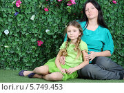 Купить «Молодая мама с дочкой на фоне живой изгороди», фото № 5749453, снято 13 января 2013 г. (c) Losevsky Pavel / Фотобанк Лори