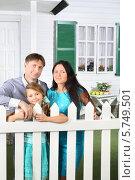 Купить «Родители с дочерью стоят у белого забора на фоне дома», фото № 5749501, снято 13 января 2013 г. (c) Losevsky Pavel / Фотобанк Лори