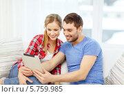 Купить «Молодые муж и жена сидят дома на диване и что-то смотрят на экране планшетного компьютера», фото № 5759985, снято 26 января 2014 г. (c) Syda Productions / Фотобанк Лори
