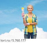 Купить «Улыбающаяся симпатичная девушка в клетчатой рубашке и желтой майке с малярной кистью в руке стоит на фоне голубого неба», фото № 5760177, снято 16 февраля 2014 г. (c) Syda Productions / Фотобанк Лори