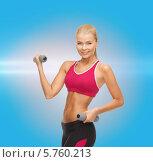 Купить «Привлекательная девушка в спортивной одежде с гантелями в руках на голубом фоне», фото № 5760213, снято 23 марта 2013 г. (c) Syda Productions / Фотобанк Лори