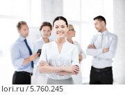 Купить «Молодая бизнес-леди улыбается, стоя на фоне коллег в офисе», фото № 5760245, снято 9 июня 2013 г. (c) Syda Productions / Фотобанк Лори