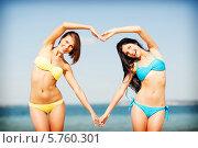 Купить «Две привлекательные девушки в бикини на фоне моря сложили сердце с помощью рук», фото № 5760301, снято 11 июля 2013 г. (c) Syda Productions / Фотобанк Лори