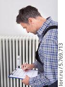 Купить «водопроводчик записывает показания прибора», фото № 5769713, снято 10 ноября 2013 г. (c) Андрей Попов / Фотобанк Лори