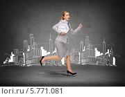 Купить «Бизнесвумен в строгом костюме держит в руках большие настенные часы и бежит на фоне серой стены с нарисованным на ней современным городом», фото № 5771081, снято 22 февраля 2020 г. (c) Syda Productions / Фотобанк Лори