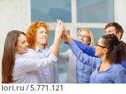 Купить «Успешные творческие молодые люди стоят, соединив ладони рук», фото № 5771121, снято 1 февраля 2014 г. (c) Syda Productions / Фотобанк Лори