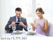 Купить «Молодые люди сидят за столиком в ресторане и фотографируют еду в тарелках на смартфон», фото № 5771161, снято 9 марта 2014 г. (c) Syda Productions / Фотобанк Лори