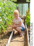 Маленькая девочка рыхлит землю в теплице. Стоковое фото, фотограф Марина Славина / Фотобанк Лори