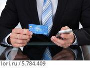 Купить «мужчина держит кредитную карту и телефон», фото № 5784409, снято 25 января 2014 г. (c) Андрей Попов / Фотобанк Лори