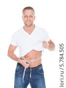Купить «спортивный мужчина измеряет объем талии», фото № 5784505, снято 25 января 2014 г. (c) Андрей Попов / Фотобанк Лори