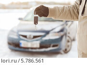 Купить «Ключи от машины в мужской руке на фоне автомобиля», фото № 5786561, снято 16 января 2014 г. (c) Syda Productions / Фотобанк Лори