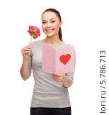 Привлекательная девушка с цветком и поздравительной открыткой. Стоковое фото, фотограф Syda Productions / Фотобанк Лори