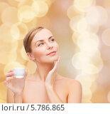 Привлекательная девушка с ухоженной кожей наносит крем на лицо. Стоковое фото, фотограф Syda Productions / Фотобанк Лори