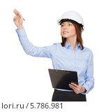 Купить «Привлекательная бизнесвумен в белой каске что-то пишет на виртуальном экране», фото № 5786981, снято 20 декабря 2013 г. (c) Syda Productions / Фотобанк Лори